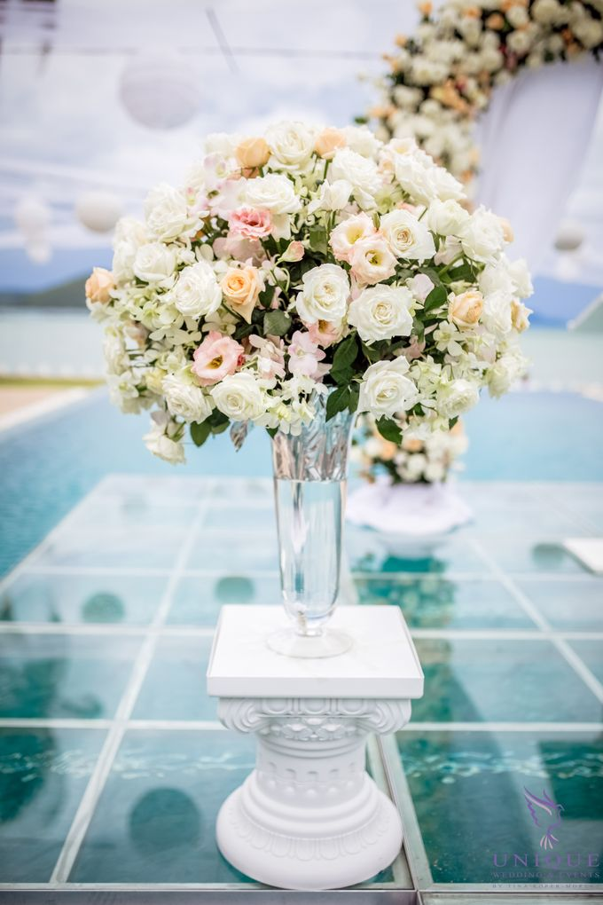 A beautiful private villa wedding featuring stunning flowers on an overwater stage. by Unique Wedding and Events - 005