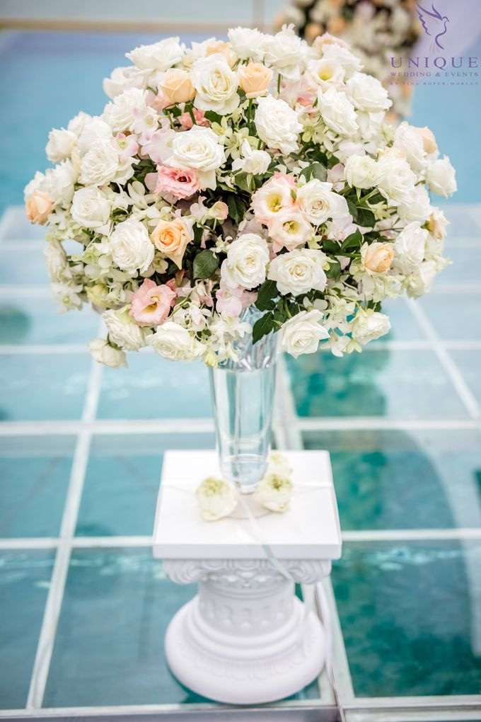 A beautiful private villa wedding featuring stunning flowers on an overwater stage. by Unique Wedding and Events - 009