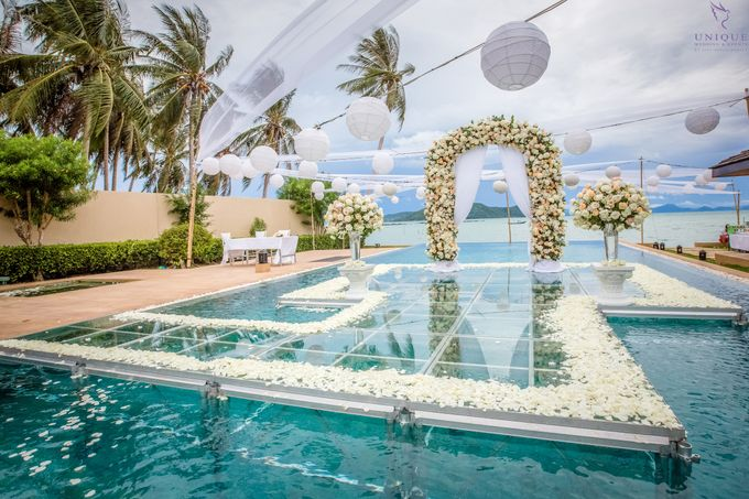 A beautiful private villa wedding featuring stunning flowers on an overwater stage. by Unique Wedding and Events - 010