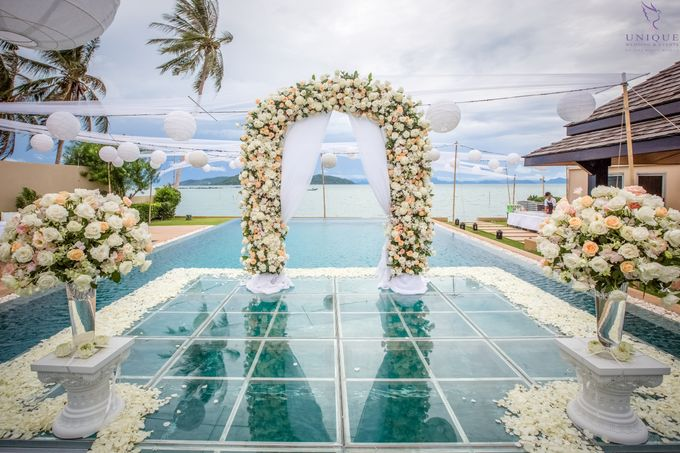 A beautiful private villa wedding featuring stunning flowers on an overwater stage. by Unique Wedding and Events - 011