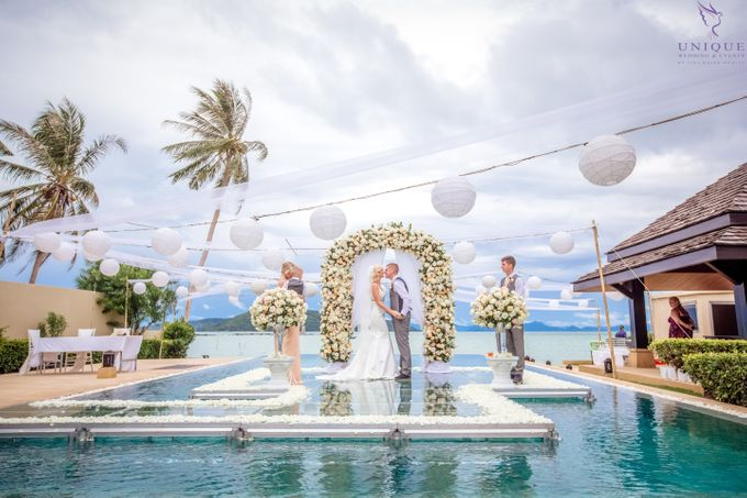 A beautiful private villa wedding featuring stunning flowers on an overwater stage. by Unique Wedding and Events - 016