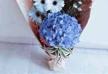 Bon Anniversaire with Limited edition dyed light-blue daisies by Floral Story Int